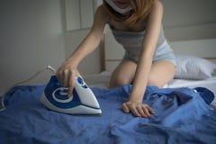 Mulher de Oung com a camisa azul passando do homem do ferro durante trabalhos domésticos fe foto de stock