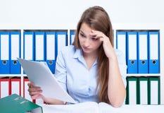 Mulher de pensamento com cabelo louro e letra no escritório Fotografia de Stock Royalty Free