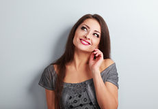 Mulher de pensamento feliz da composição que olha acima com mão perto da cara no bl Imagens de Stock Royalty Free