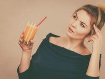Mulher de pensamento que guarda o suco de laranja fresco Fotos de Stock