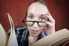 Mulher de Peprlexed com olhos grandes que lê um livro Imagem de Stock
