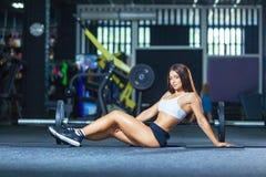 Mulher de pernas longas apta que senta-se no assoalho no gym perto do barbell fotografia de stock
