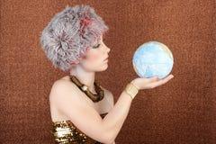 Mulher de prata do ouro da forma que olha o mapa global Imagens de Stock