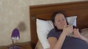 Mulher de relaxamento que encontra-se na cama e em ler a mensagem no email no telefone celular Texto que datilografa no telefone filme
