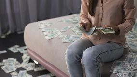 Mulher de Rich Asian que senta-se no sofá e que conta o dinheiro, multimilionário fêmea filme