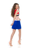 Mulher de riso em Mini Dress Walking And Looking sobre o ombro Fotos de Stock Royalty Free