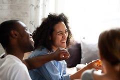 Mulher de riso feliz da raça misturada que come a pizza, falando com amigos fotografia de stock
