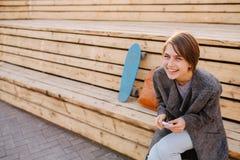 A mulher de riso nova com um skate est? sentando-se em um banco de 2 fases fotografia de stock royalty free