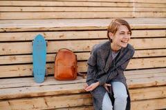 A mulher de riso nova com um skate est? sentando-se em um banco de 2 fases fotos de stock royalty free
