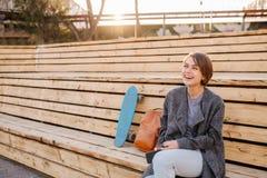 A mulher de riso nova com um skate est? sentando-se em um banco de 2 fases imagens de stock royalty free