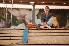 A mulher de riso nova com um skate est? sentando-se em um banco de 2 fases fotos de stock