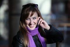 Mulher de riso nova nos óculos de sol com telefone imagens de stock royalty free