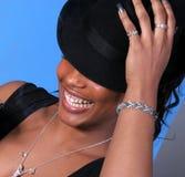 A mulher de riso prende o chapéu fotografia de stock royalty free