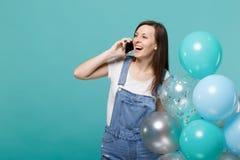 A mulher de riso que fala no telefone celular, conversação agradável de condução, comemorando guarda balões de ar coloridos imagens de stock