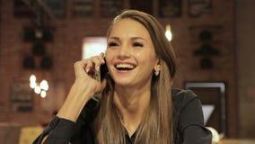 Mulher de Smartphone que fala no telefone que ri no café video estoque