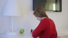 A mulher de Smileing pensa e começa-a escrever a letra em uma tabela branca filme