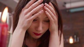 Mulher de sofrimento bonita que guarda sua cabeça em suas mãos filme