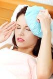 Mulher de sofrimento com um gelo-ruim em sua cabeça. Imagens de Stock