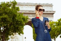 Mulher de solo do turista com o copo do latte da soja que fala no móbil foto de stock