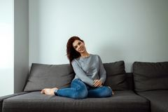 Mulher de sonho nova que senta-se no sof? em casa Jovem mulher pensativa que senta-se na sala de visitas e que olha acima Mulher  fotografia de stock royalty free