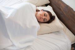 A mulher de sono acordou na manhã após o sono fotos de stock