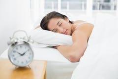Mulher de sono com o despertador borrado na tabela de cabeceira Fotos de Stock Royalty Free