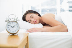 Mulher de sono com o despertador borrado no primeiro plano Foto de Stock Royalty Free