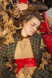 A mulher de sono encontrou-se para baixo no assoalho completamente das folhas Madeiras no outono fotografia de stock