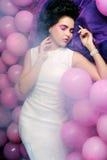 Mulher de sono que encontra-se no assoalho entre balões Imagens de Stock Royalty Free
