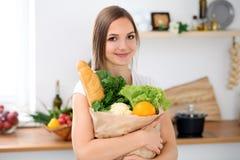 A mulher de sorriso alegre nova está pronta para cozinhar em uma cozinha A dona de casa está mantendo o saco de papel grande comp Imagem de Stock