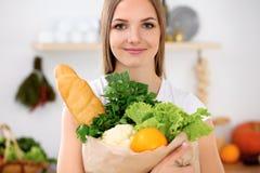 A mulher de sorriso alegre nova está pronta para cozinhar em uma cozinha A dona de casa está mantendo o saco de papel grande comp Fotografia de Stock