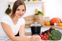 A mulher de sorriso alegre nova está pronta para cozinhar em uma cozinha Dona de casa que senta-se na tabela e que olha a câmera Imagens de Stock