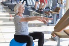 Mulher de sorriso apta feliz que exercita e que usa a bola Fotografia de Stock Royalty Free