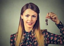Mulher de sorriso atrativa do retrato que sustenta o grupo de chaves que pertencem a seu casa ou carro fotos de stock