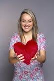 Mulher de sorriso atrativa que guarda um coração vermelho Fotografia de Stock