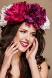 Mulher de sorriso bonita com as flores brilhantes em sua cabeça Face tocante Fotos de Stock