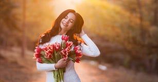 Mulher de sorriso bonita com as flores da mola no fundo do por do sol imagem de stock royalty free