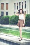 Mulher de sorriso bonita com cabelo encaracolado Olhar elegante urbano Imagem de Stock Royalty Free