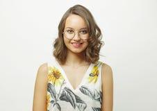 A mulher de sorriso bonita com espetáculos redondos, veste o t-shirt do verão, tem caucasians aparência, encantamento do olhar, i fotografia de stock royalty free