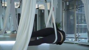 Mulher de sorriso bonita com o corpo atrativo que faz a ioga aérea antigravitante que gerencie ao redor na rede na aptidão filme