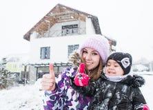 Mulher de sorriso bonita com os polegares da criança pequena acima no fundo grande da casa de campo Imagens de Stock