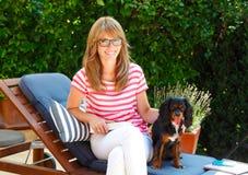 Mulher de sorriso bonita com seu cachorrinho Foto de Stock