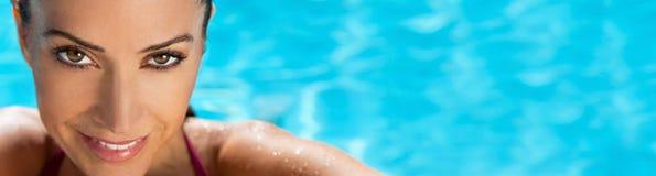 Mulher de sorriso bonita da bandeira do panorama que relaxa na piscina foto de stock