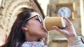 Mulher de sorriso bonita do close up nos óculos de sol que bebe o fundo da construção histórica de copo de papel do café filme