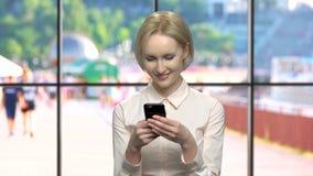 Mulher de sorriso bonita do escritório que usa o telefone celular vídeos de arquivo