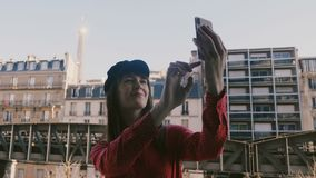 Mulher de sorriso bonita feliz do turista que toma a foto do selfie do smartphone com opinião da torre Eiffel em Paris do balcão  video estoque