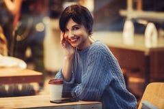 Mulher de sorriso bonita no café com café interior e bebendo acolhedor morno fotos de stock royalty free