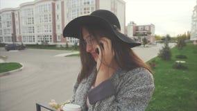 Mulher de sorriso bonita nova no chapéu negro e nos vidros que fala no telefone celular video estoque