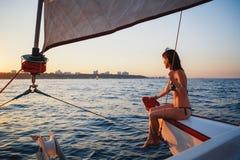 Mulher de sorriso bonita nova no iate luxuoso no mar, olhando para a frente, tempo da noite do por do sol fotos de stock royalty free