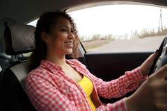 Mulher de sorriso bonita nova que conduz um carro Sua filha bonito que senta-se na parte traseira e que aprecia foto de stock